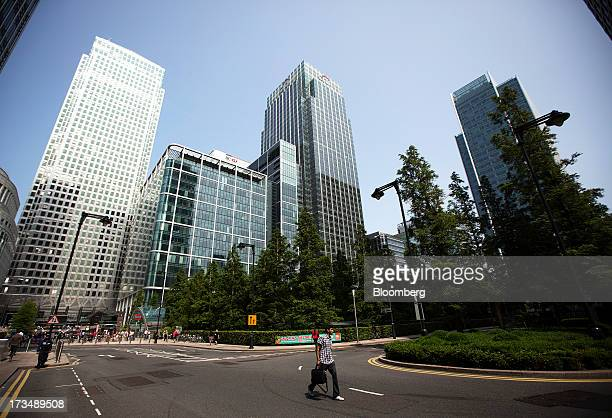 Pedestrian walks along a road past No. 1 Canada Square, also known as Canary Wharf Tower, left, and Citigroup Inc.'s offices, right, in the Canary...
