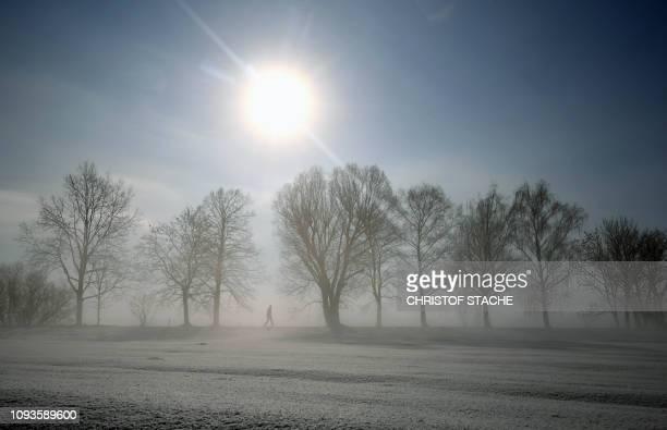 TOPSHOT A pedestrian walks along a snowcovered alley near the small Bavarian village of Eichenau near Munich southern Germany during nice foggy...