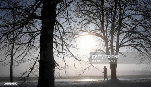 A pedestrian walks along a snowcovered alley near the small Bavarian village of Eichenau near Munich southern Germany during nice foggy winter...