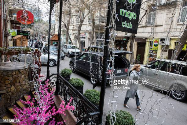 A pedestrian walks along a street past clubs and bars in Baku Azerbaijan on Friday March 16 2018 Azerbaijan's economy barely returned to growth last...