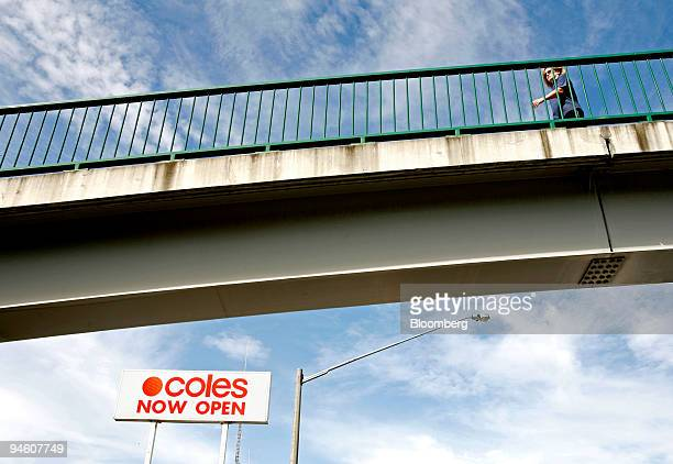 A pedestrian walks along an overpass above a Coles Group Ltd supermarket in Sydney Australia on Tuesday May 8 2007
