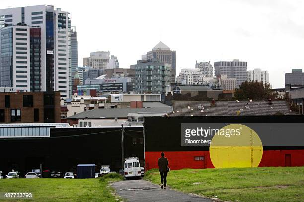 A pedestrian walks along Eveleigh Lane past a mural of the Aboriginal flag at The Block a plot of land owned by the Aboriginal Housing Company in the...