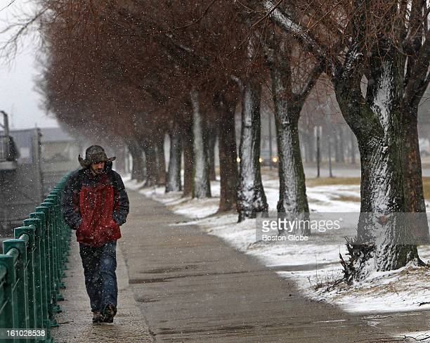 A pedestrian walks along Memorial Drive in Cambridge as snow began to accumulate at midday