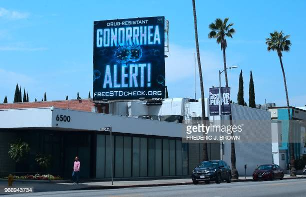 A pedestrian walks along Sunset Boulevard in Hollywood California on May 29 2018 beneath a billoard from the AIDS Healthcare Foundation warning of a...