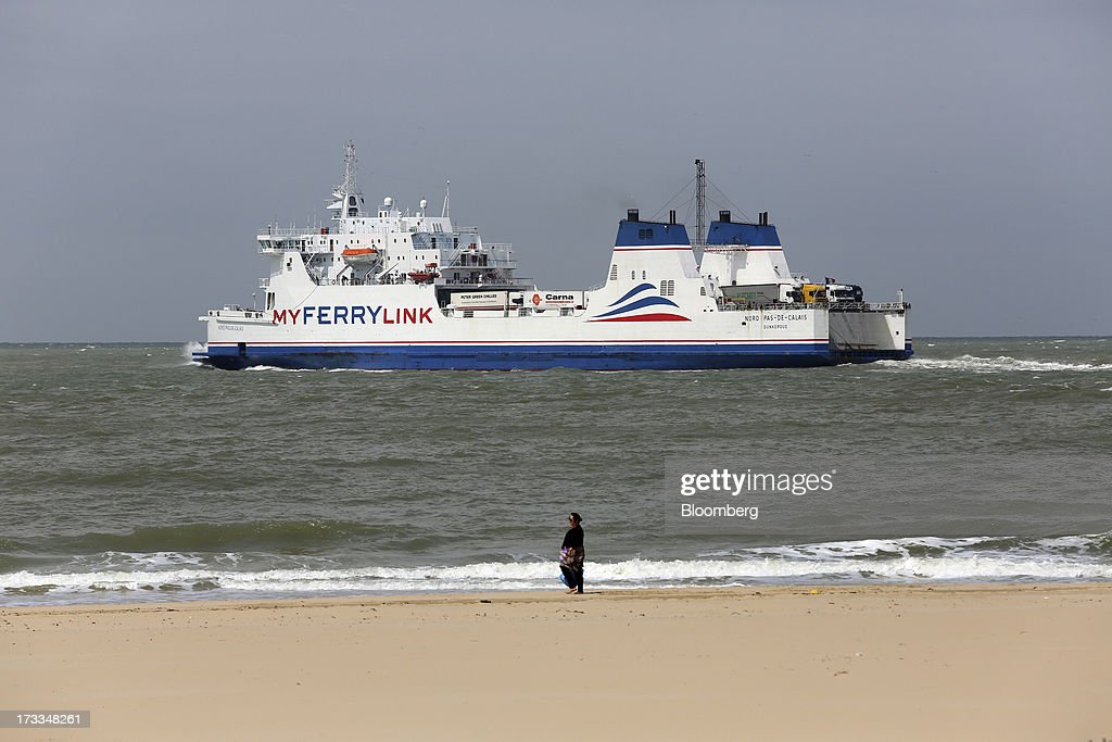 A pedestrian walks along the beach as the 'Nord Pas De Calais' roll-on, roll-off (RoRo) ferry, operated by MyFerryLink, a unit of Groupe Eurotunnel SA, leaves the Port of Calais in Calais, France, on Thursday, July 11, 2013. Eurotunnel was barred by the U.K. Competition Commission from operating a ferry service between France and Dover in the U.K. on concern it would give it too much dominance on the Channel traffic route. Photographer: Chris Ratcliffe/Bloomberg via Getty Images