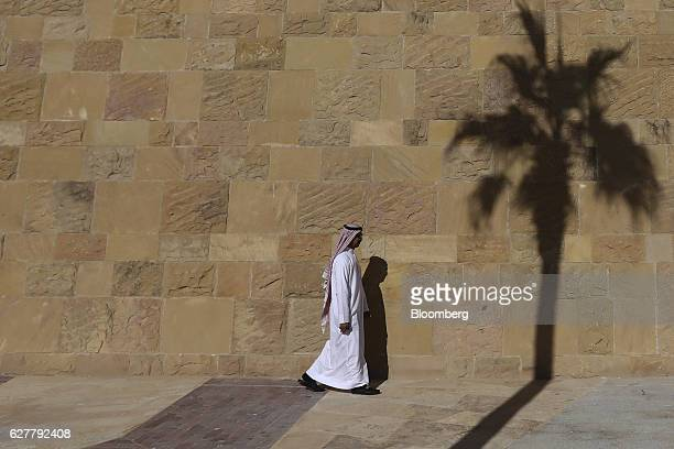 A pedestrian walks along the sidewalk and past the shadow of a palm tree at the King Abdullah Financial District in Riyadh Saudi Arabia on Thursday...