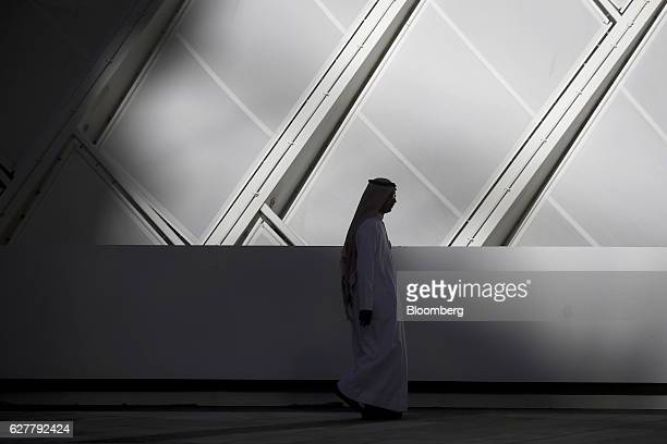 A pedestrian walks along the sidewalk through buildings under construction including offices apartments hotels conference centres a mosque and...