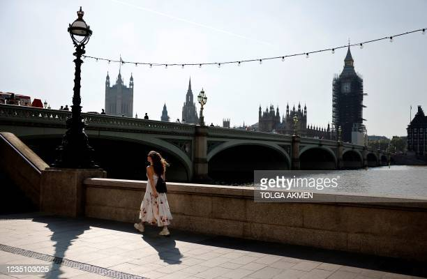 Pedestrian walks along the south bank of hte River Thames, opposite the Houses of Parliament in London on September 7, 2021. - Breaking an election...