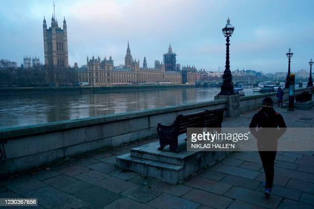 Pedestrian walks along the southern bank of the River Thames with Britain's Houses of Parliament across the river at sunrise in London on December...