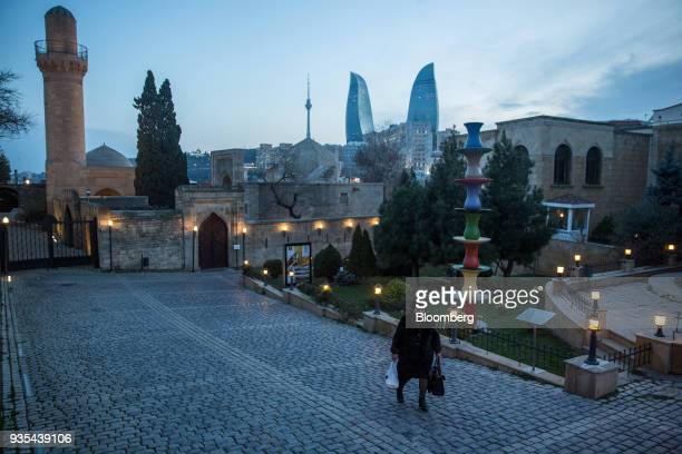 A pedestrian walks as skyscrapers of the Flame Towers stand in the background in the Old City of Baku Azerbaijan on Friday March 16 2018 Azerbaijan's...
