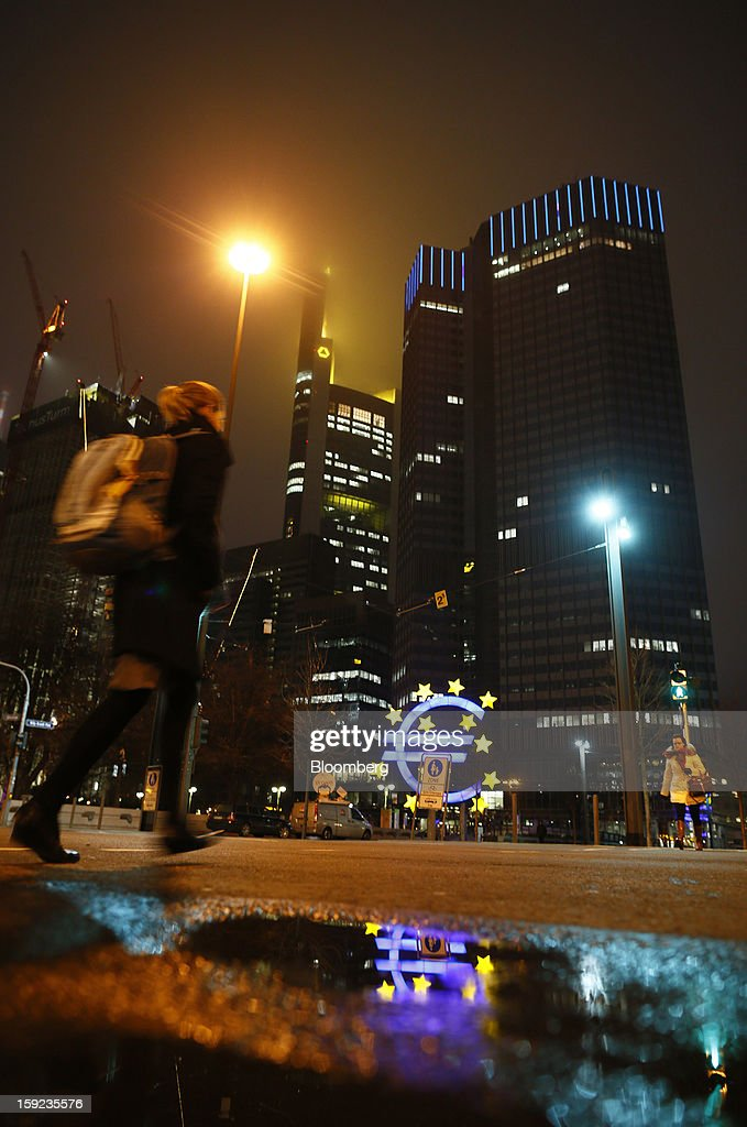 A pedestrian walks at night under street lights past the European Central Bank (ECB) headquarters in Frankfurt, Germany, on Wednesday, Jan. 9, 2013. German two-year notes declined, pushing yields to the highest in 11 weeks, after European Central Bank President Mario Draghi said the decision to leave the key interest rate at 0.75 percent was 'unanimous.' Photographer: Ralph Orlowski/Bloomberg via Getty Images