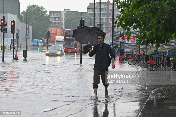 Pedestrian walks bare-footed along a flooded road in The Nine Elms district of London on July 25, 2021 during heavy rain. - Buses and cars were left...