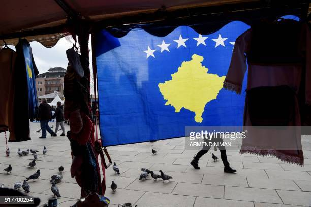 TOPSHOT A pedestrian walks behind Kosovo flag displayed in Pristina on February 13 ahead of the tenth anniversary of Kosovo independence Kosovo...