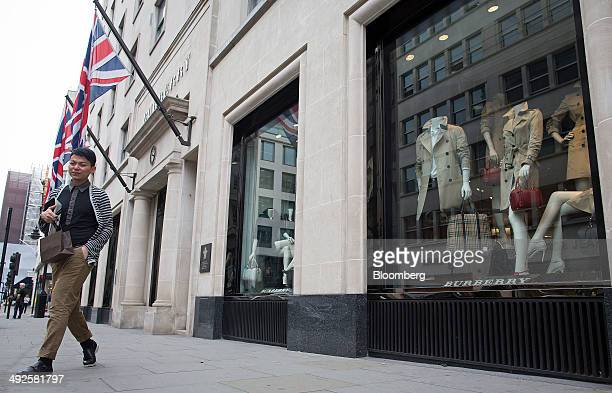 A pedestrian walks beneath British Union flags as he passes a Burberry fashion store operated by Burberry Group Plc on New Bond Street in London UK...