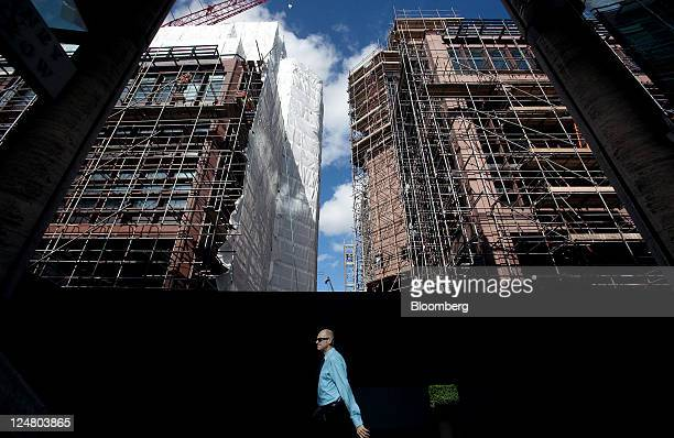 Pedestrian walks between buildings number 4 and 5 Broadgate as construction work is underway on the new London headquarters for UBS AG at the site...