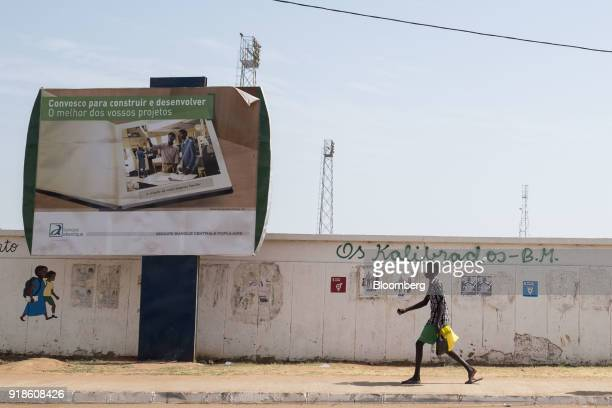 A pedestrian walks by a Banque Atlantique billboard in Bissau GuineaBissau on Saturday Feb 10 2018 The International Monetary Fund said an increase...