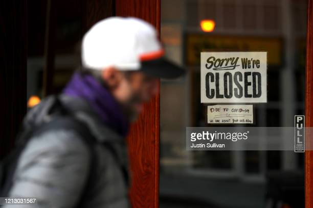 A pedestrian walks by a closed sign on the door of a restaurant on March 17 2020 in San Francisco California Seven San Francisco Bay Area counties...