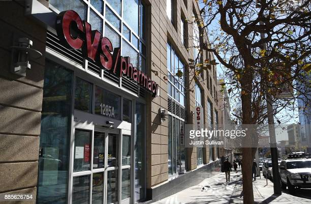 A pedestrian walks by a CVS Pharmacy on December 4 2017 in San Francisco California Drugstore chain CVS Health Corp announced plans on Sunday to...