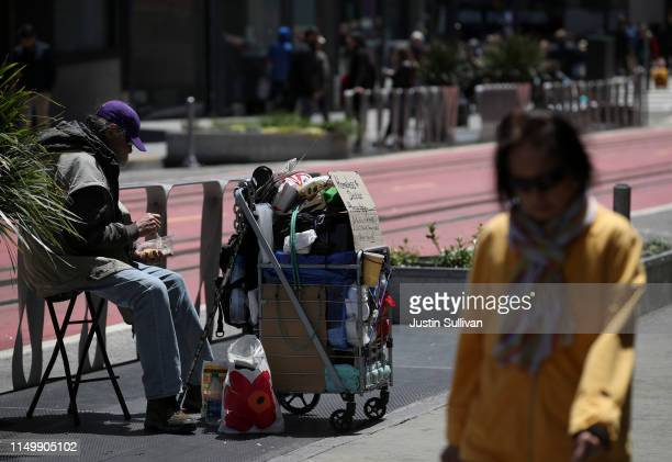 A pedestrian walks by a homeless man who is begging for money on May 17 2019 in San Francisco California Results of a twoyear Homelessness...