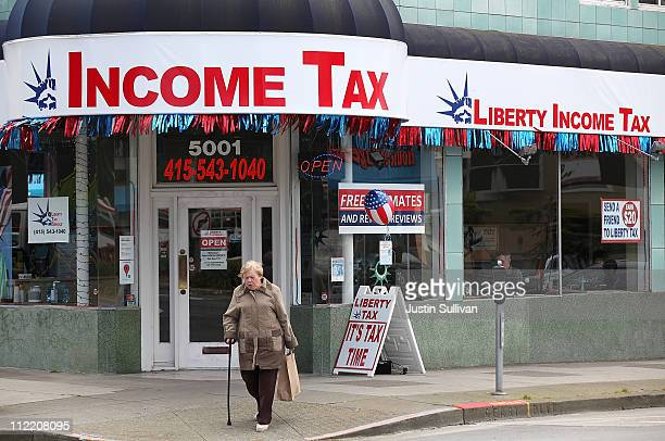 A pedestrian walks by a Liberty Tax Services tax preparation office on April 14 2011 in San Francisco California Despite having an extra three days...