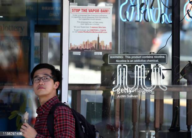 A pedestrian walks by a neon sign advertising Juul ecigarettes on June 25 2019 in San Francisco California The San Francisco Board of Supervisors...