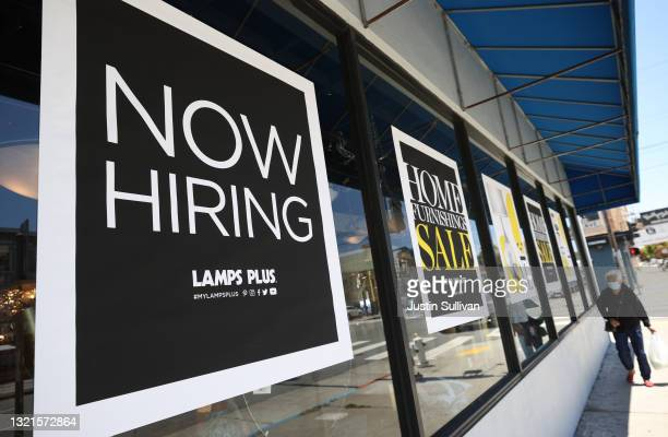 Pedestrian walks by a Now Hiring sign outside of a Lamps Plus store on June 03, 2021 in San Francisco, California. According to a U.S. Labor...