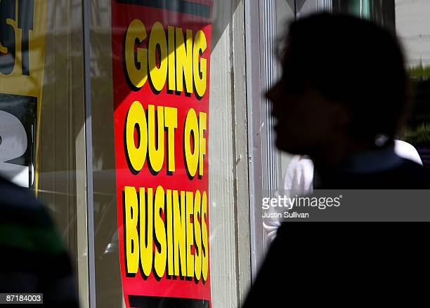 A pedestrian walks by a sign announcing a going out of business sale May 13 2009 in San Francisco California The commerce department reported today...