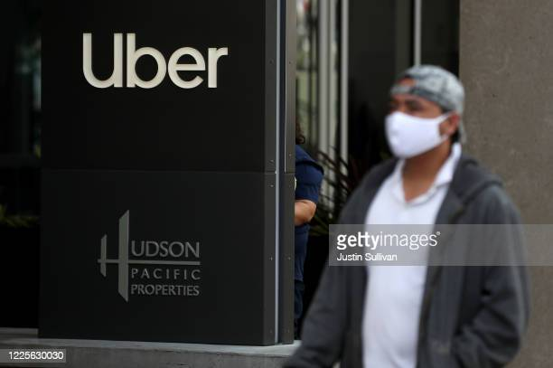 Pedestrian walks by a sign in front of the Uber headquarters on May 18, 2020 in San Francisco, California. Uber announced plans to cut 3,000 jobs and...