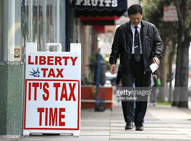 A pedestrian walks by a sign outside of a Liberty Tax Services tax preparation office on April 14 2011 in San Francisco California Despite having an...