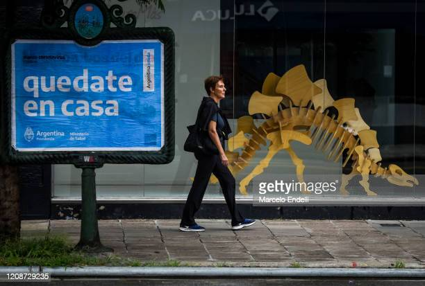 A pedestrian walks by a sign that reads 'stay home' on March 31 2020 in Buenos Aires Argentina Last Sunday President Fernandez announced an extension...