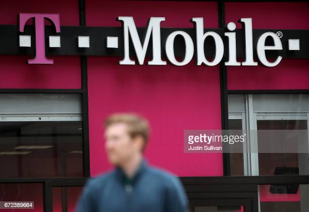 A pedestrian walks by a TMobile store on April 24 2017 in San Francisco California TMobile will report first quarter earnings today after the closing...