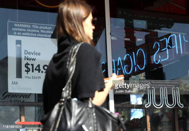 Pedestrian walks by a window advertisement for Juul products on October 17, 2019 in San Francisco, California. Juul announced plans to immediately...