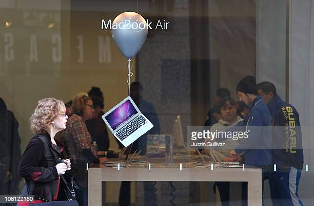 A pedestrian walks by a window display of the MacBook Air at an Apple retail store on January 18 2011 in San Francisco California Apple will release...