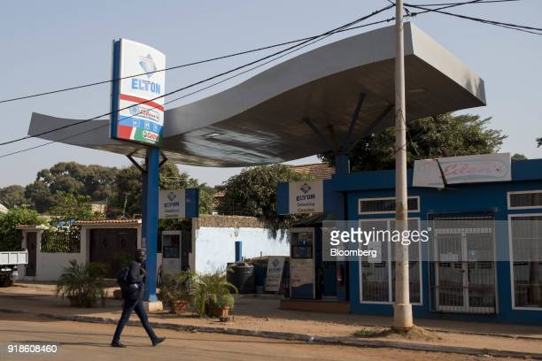 A pedestrian walks by an Elton Oil Co gas station in Bissau GuineaBissau on Monday Feb 12 2018 The International Monetary Fund said an increase in...