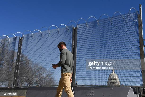 Pedestrian walks by fencing that surrounds the United States Capitol on Thursday February 25, 2021 in Washington, DC. The fencing went up following...