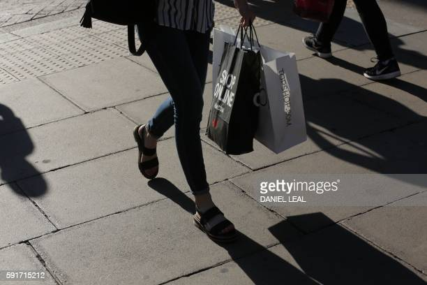 A pedestrian walks carrying a shopping bag in Oxford Street in central London on August 17 2016 Retail sales in Britain a key driver of the country's...