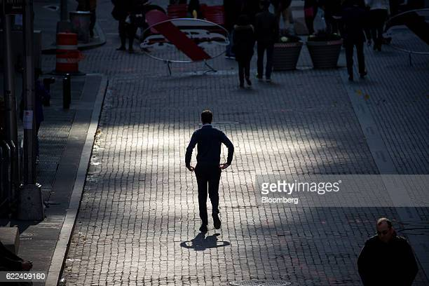 A pedestrian walks down Broad Street in front of the New York Stock Exchange in New York US on Friday Nov 11 2016 US stocks fluctuated in whipsaw...