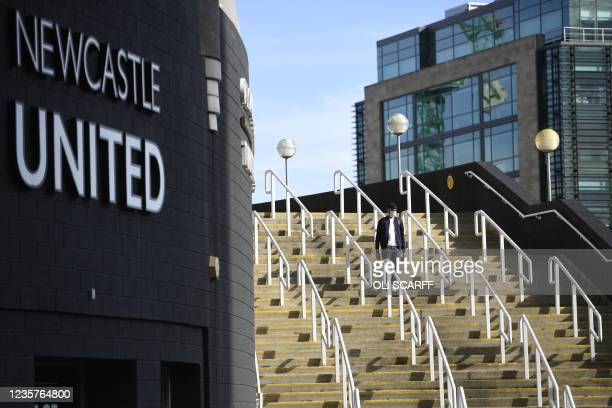 Pedestrian walks down steps outside Newcastle United's stadium St James' Park in Newcastle upon Tyne in northeast England on October 8 after the sale...