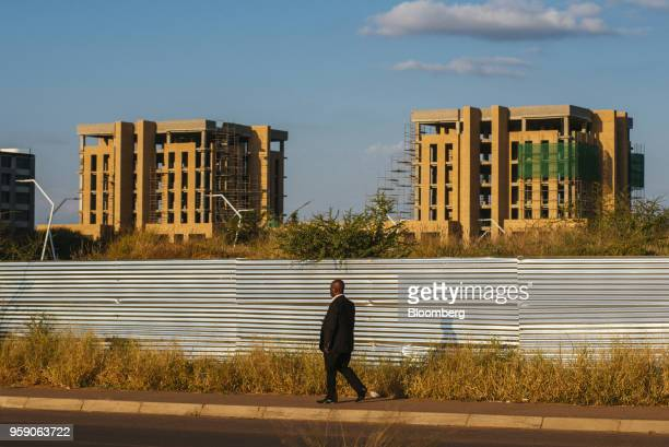 A pedestrian walks down the street as underconstructions buildings stand beyond in the central business district of Gaborone Botswana on Monday May...