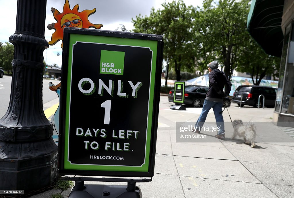 A pedestrian walks her dog by a sign in front of an H&R Block office on April 16, 2018 in Oakland, California. Taxpayers who have procrastinated on filing their returns will have an additional two days to file tax returns since April 15th fell on a Sunday and Emancipation Day is observed on Moday April 16th.