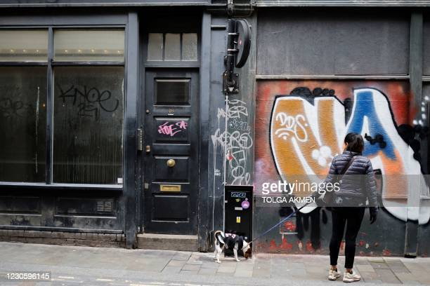 Pedestrian walks her dog past closed shops in the City of London on January 15 during the third coronavirus lockdown. - Britain's economy slumped 2.6...