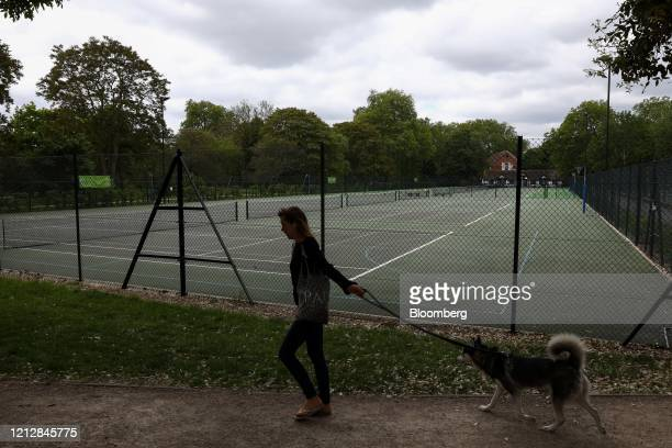 Pedestrian walks her dog past empty tennis courts in The Regent's Park in London, U.K., on Wednesday, May 13, 2020. The U.K. Will begin taking what...
