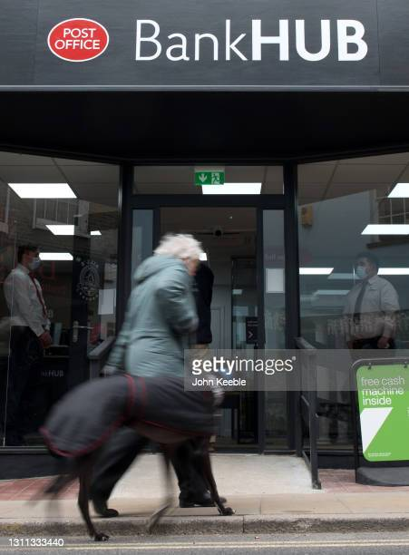 Pedestrian walks her dog past the new Bank Hub on April 7, 2021 in Rochford, England. The new shared 'Banking Hub' organised by the 'Community Access...
