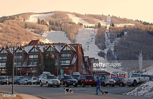 A pedestrian walks his dogs across the street in Park City Utah US on Friday Jan 13 2012 The Sundance Film Festival will run from Jan 19 29...