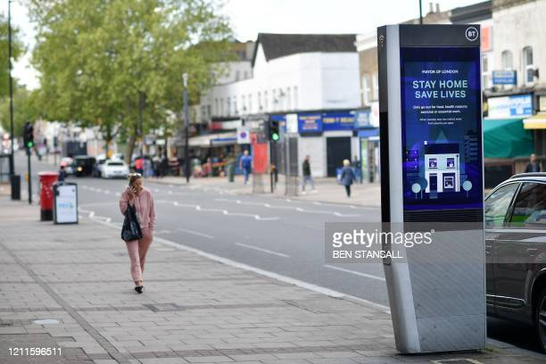 Pedestrian walks in a street where an electronic billboard urges the public to stay at home in the London borough of Newham, east London, on May 2 as...