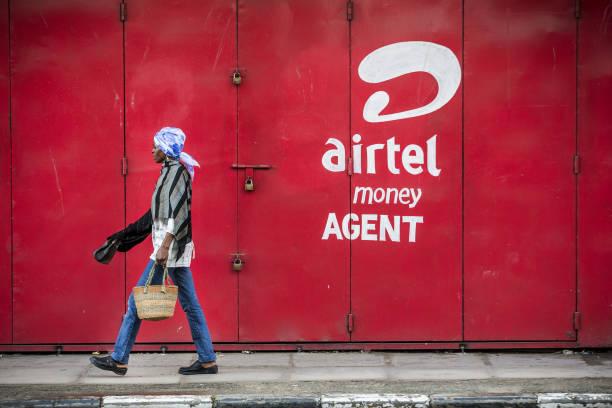 pedestrian walks in front of a bharti airtel ltd money agent shop in picture