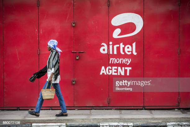 A pedestrian walks in front of a Bharti Airtel Ltd money agent shop in Mombasa Kenya on Thursday Nov 23 2017 The countrys Treasury has already cut...