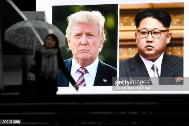 TOPSHOT A pedestrian walks in front of a huge screen flashing a news report relating to US President Donald Trump and North Korean leader Kim Jong...