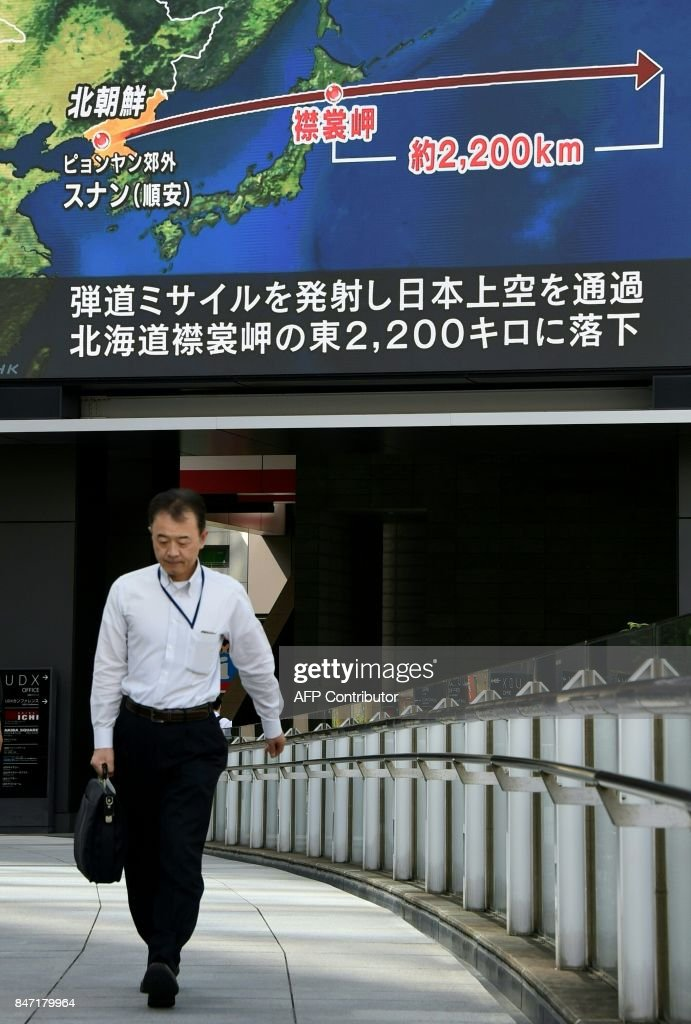 A pedestrian walks in front of a large video screen in Tokyo broadcasting a news report about North Korea's latest missile test that passed over Japan on September 15, 2017. North Korea fired a ballistic missile over Japan and into the Pacific on September 15, responding to new UN sanctions with what appeared to be its furthest-ever missile flight amid high tensions over its weapons programmes. / AFP PHOTO / Toru YAMANAKA