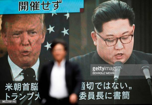 TOPSHOT A pedestrian walks in front of a screen in Tokyo on May 25 2018 flashing a news report relating to US President Donald Trump cancelling his...